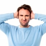 irritated man blocking his ears by stockimages